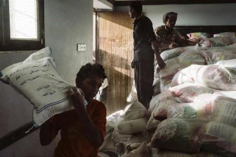 Laborers move sacks of flour at a school located a few miles from the front line.